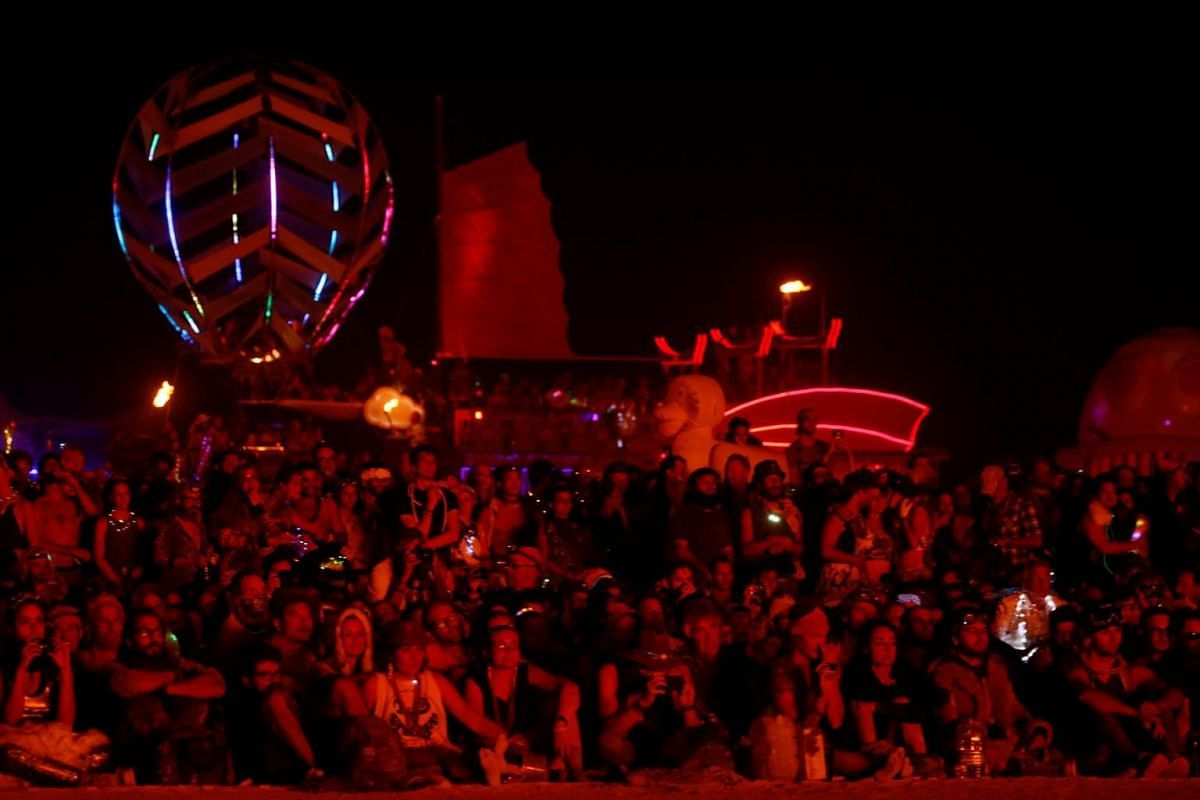Burning Man participants gather by the thousands in front of a circle of large art cars to watch the effigy of The Man burn at the culmination of the annual Burning Man arts and music festival in the Black Rock desert of Nevada, on Sept 2, 2017.