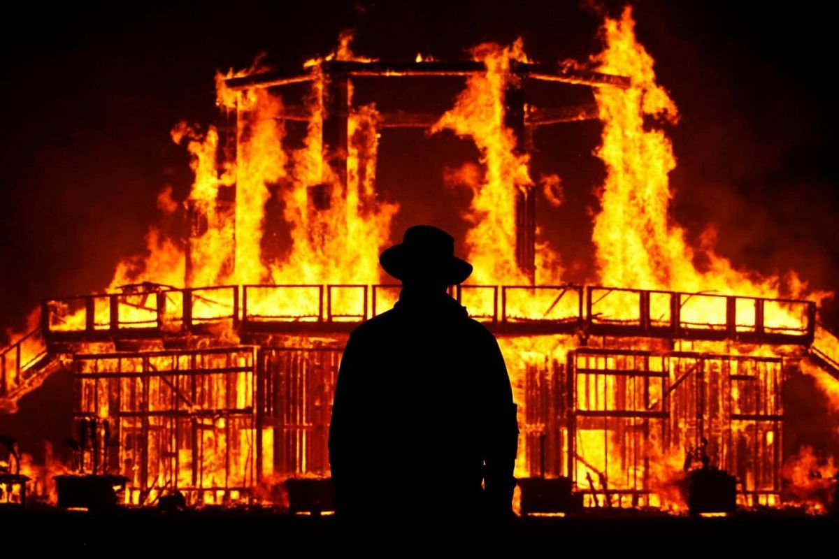 A Burning Man Ranger guards the inner perimeter around the effigy of The Man as it burns on Sept 2, 2017.