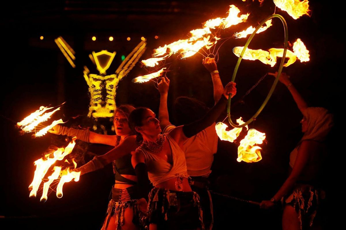 Burning Man participants from the Revolutionary Motion fire conclave spin fire in front of the effigy of The Man on Sept 2, 2017.