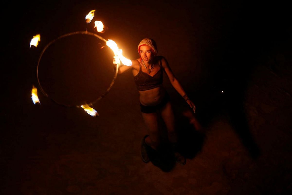 A participant dances with fire before the Man Burn as approximately 70,000 people from all over the world gathered on Sept 2, 2017.