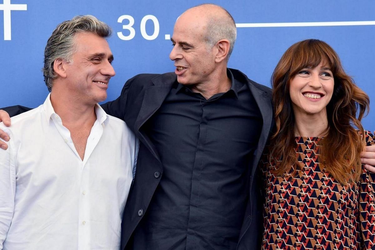 Israeli actors Lior Ashkenazi (left) and Sarah Adler (right) posing with director Samuel Maoz (centre) during a photocall for Foxtrot, on Sept 2, 2017.