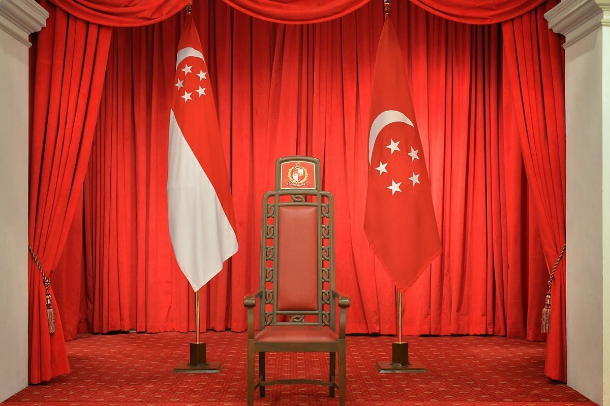 The president's chair, flanked by the State flag and the Presidential flag, at the Istana.