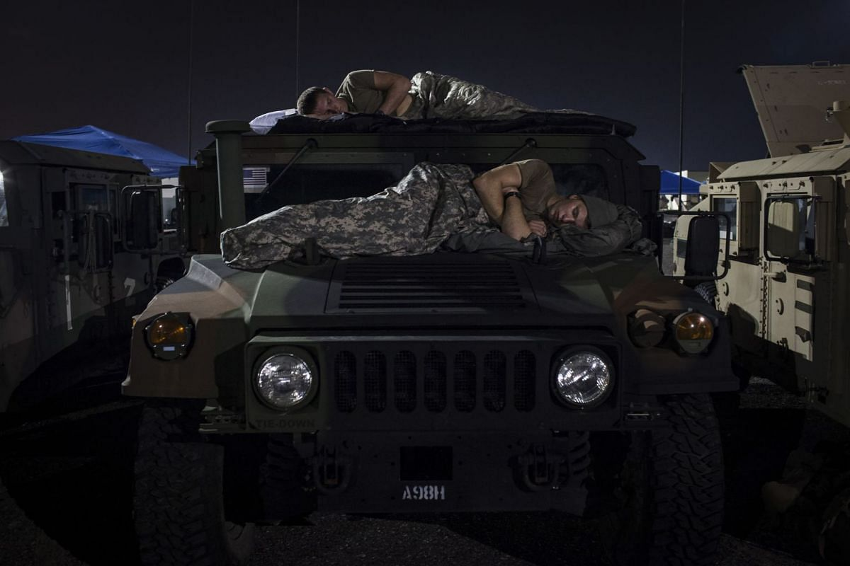 Soldiers of the of the 1st Battalion (Airborne), 143rd Infantry Regiment of the Texas Army National Guard sleep in the parking lot of a Sears store where his unit is staging operations in Port Arthur, Texas, Sept. 3, 2017. PHOTO: THE NEW YORK TIMES