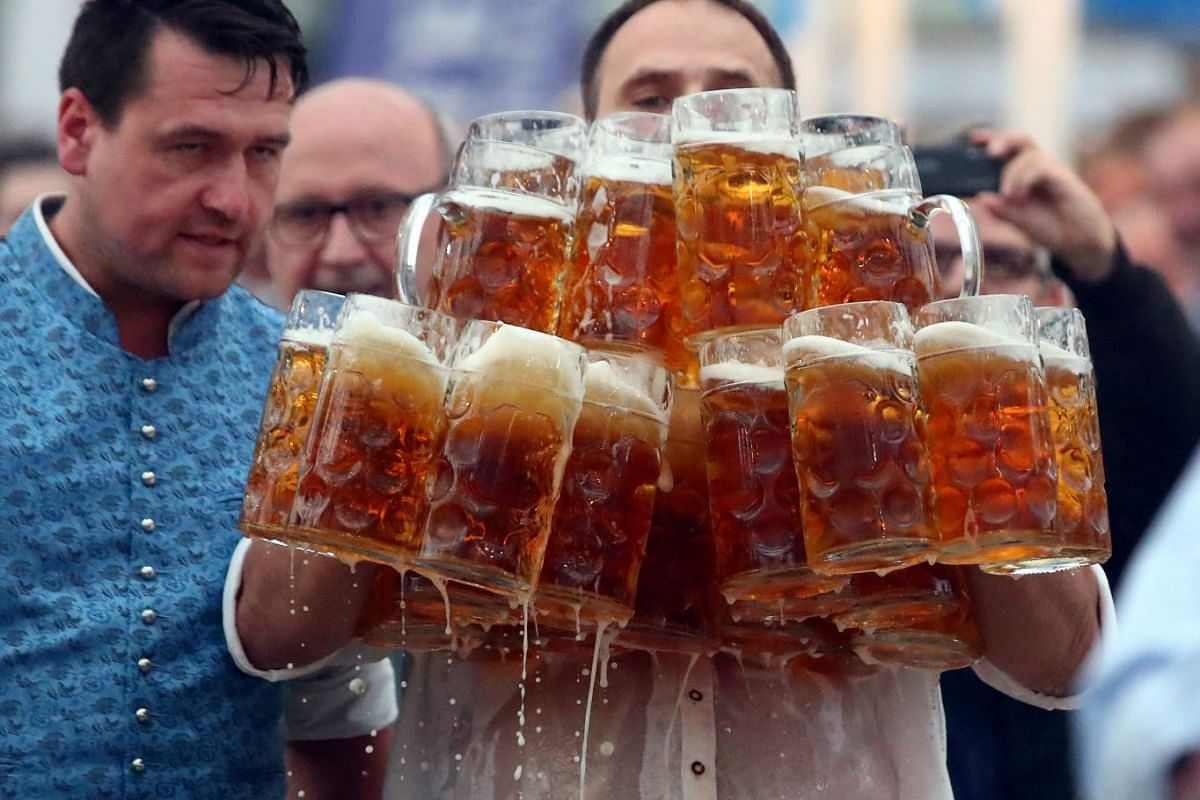 German Oliver Struempfel competes to set a new world record in carrying one liter beer mugs over a distance of 40 m (131 ft 3 in) in Abensberg, Germany September 3, 2017. Struempfel carried 29 mugs over 40 meters to set a new world record. PHOTO: REU