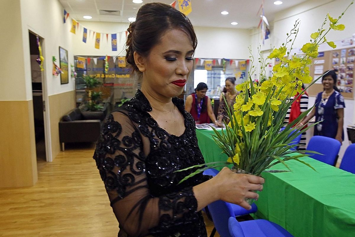 Wearing a traditional Indonesian dress, Filipina Jenny Ifurung, 41, is seen here preparing a bouquet for Hari Raya celebrations at the clubhouse in July. A trained teacher in the Philippines, Ms Ifurung is responsible for the clubhouse's decorations. She
