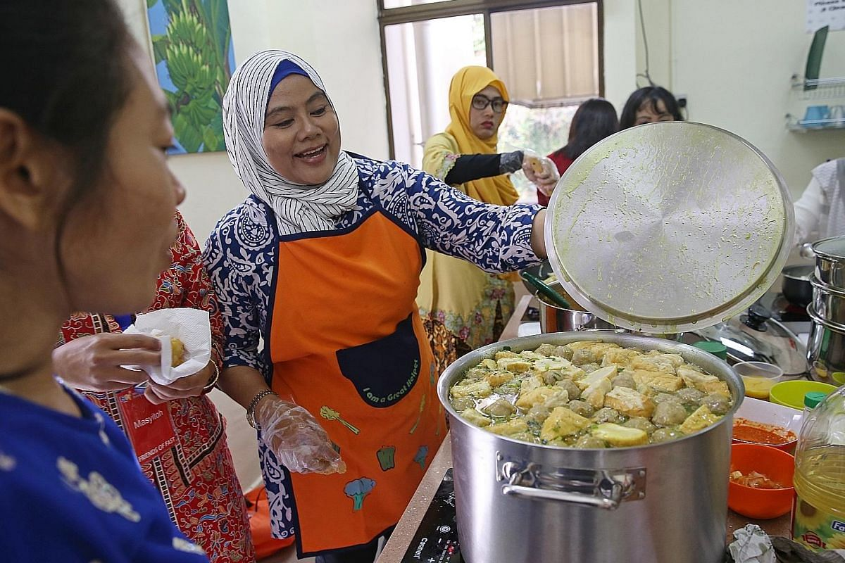 "Ms Atik Setyamurti, 42, getting ready to taste a pot of ""bakso"" (Indonesian meatball soup) which she and several other Indonesian friends prepared for the Hari Raya celebrations in July. The Indonesians spent the whole morning cooking food at the clubhous"
