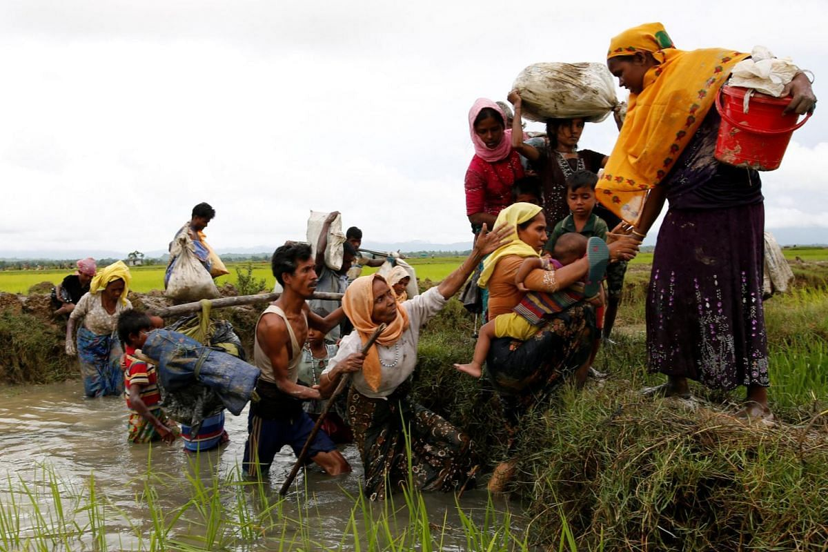 A group of Rohingya refugees cross a canal after travelling over the Bangladesh-Myanmar border in Teknaf, Bangladesh, on Sept 1, 2017.