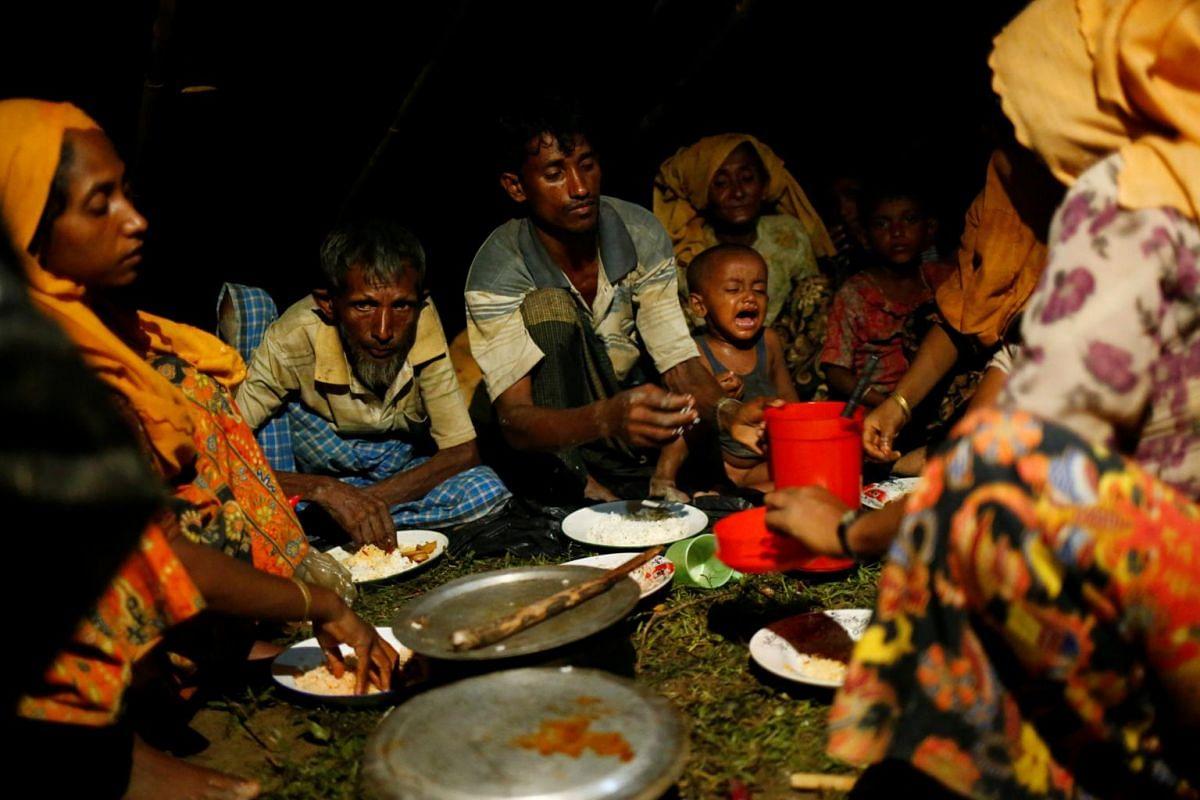 Rohingya refugees having dinner at a makeshift shelter near Gundum in Cox's Bazar, on Sept 3, 2017.