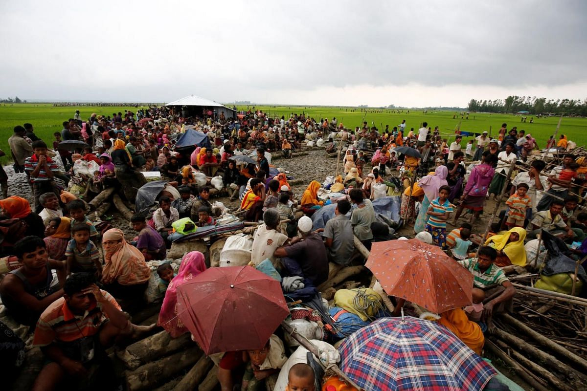 Rohingya refugees sit as they are temporarily held by the Border Guard Bangladesh (BGB) in an open area after crossing the border, in Teknaf, on Sept 3, 2017.