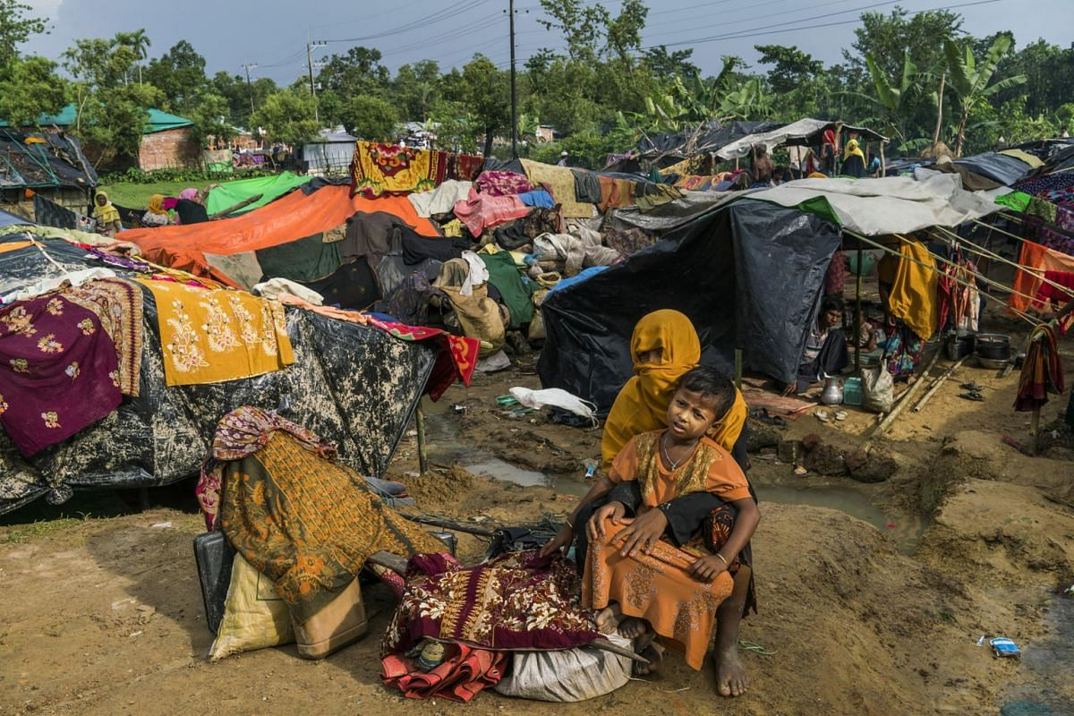 Rohingya refugees who have recently arrived, wait with their belongings in the overflowing Kutupalong refugee camp in Ukhia, Bangladesh, on Sept 2, 2017.