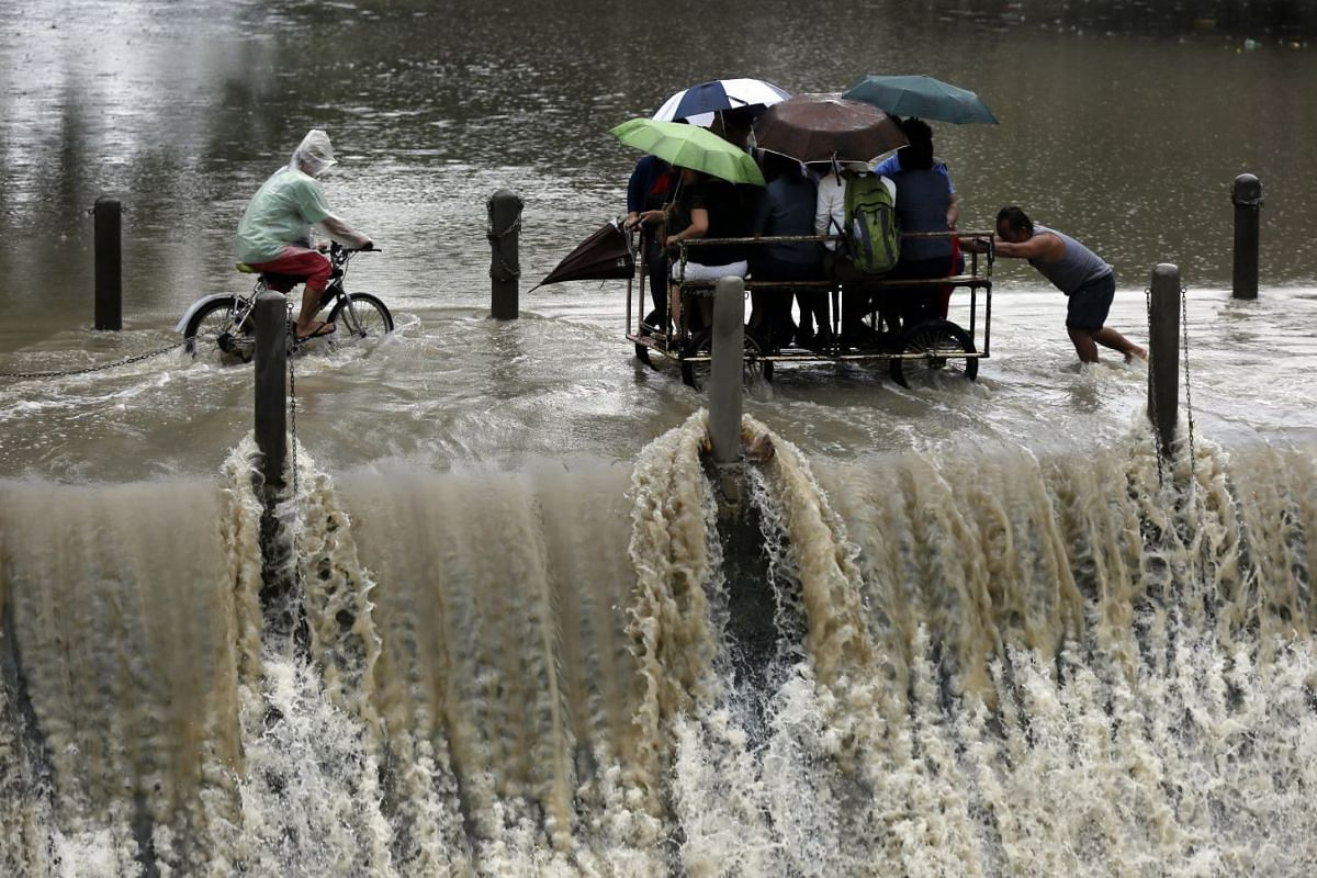 Filipinos riding on a makeshift cart cross over an overflowing dam during a downpour in Las Pinas city, south of Manila, Philippines, September 5, 2017. PHOTO: EPA