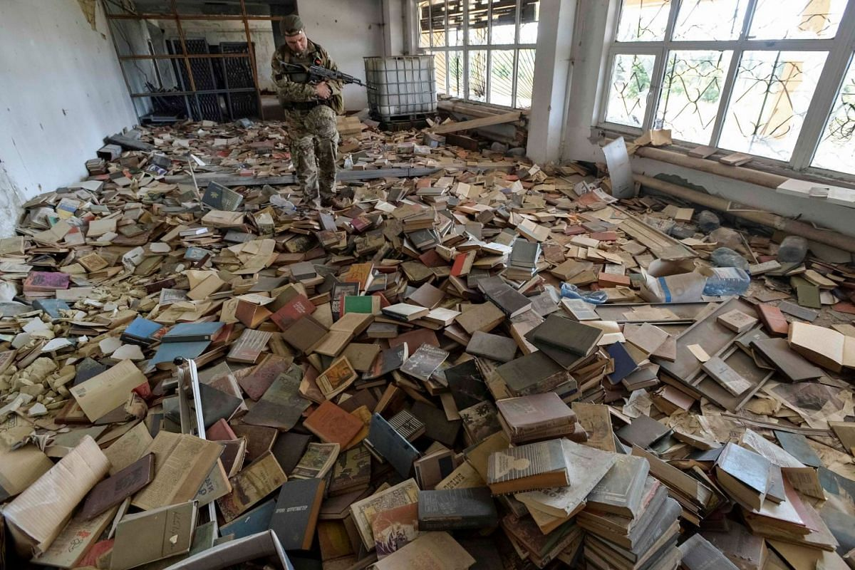 A Ukrainian serviceman inspects an abandoned library, with numerous books seen on the floor, near his position on the front line in the town of Maryinka, Ukraine September 3, 2017. PHOTO: REUTERS