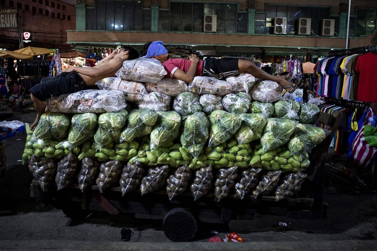 Workers sleep on top of vegetables on a wooden cart in Divisoria market in Manila on September 4, 2017. PHOTO: AFP