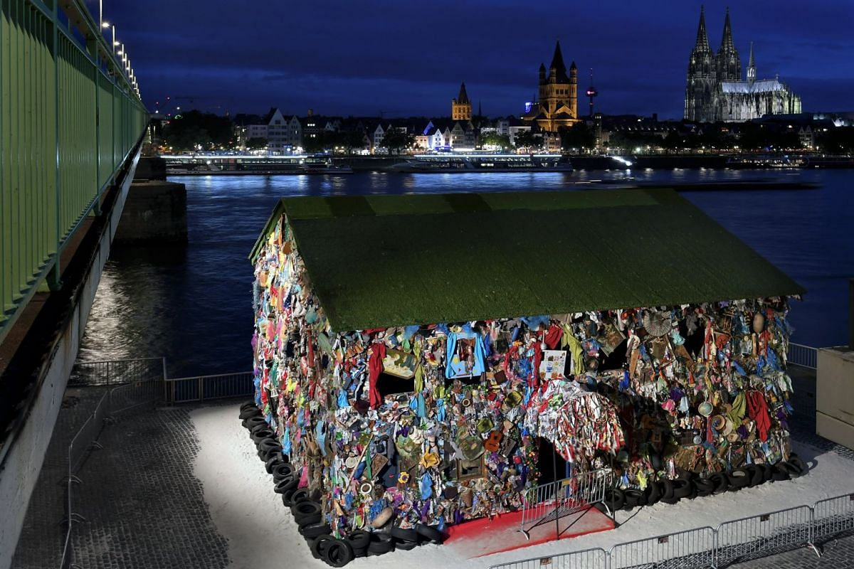 An exterior view of the sculpture 'Save The World Hotel' by German artist HA Schult at Deutzer Werft in Cologne, Germany, September 4, 2017. The outer walls of a wooden house are dressed in garbage, e.g. plastic bottles, rags, newspapers, but also an