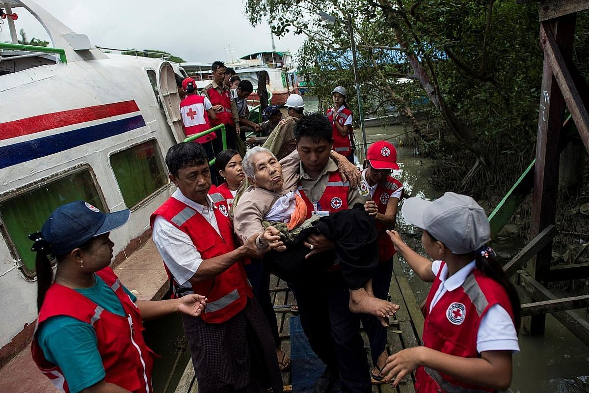 Members of Myanmar's Red Cross carrying an elderly woman from a conflict area, as she arrived at the Sittwe jetty, in Rakhine state, last Wednesday.