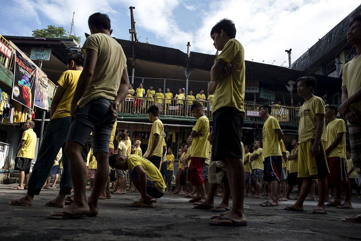 Inmates attending a flag raising ceremony inside the Quezon City Jail in Manila on July 11, 2017.