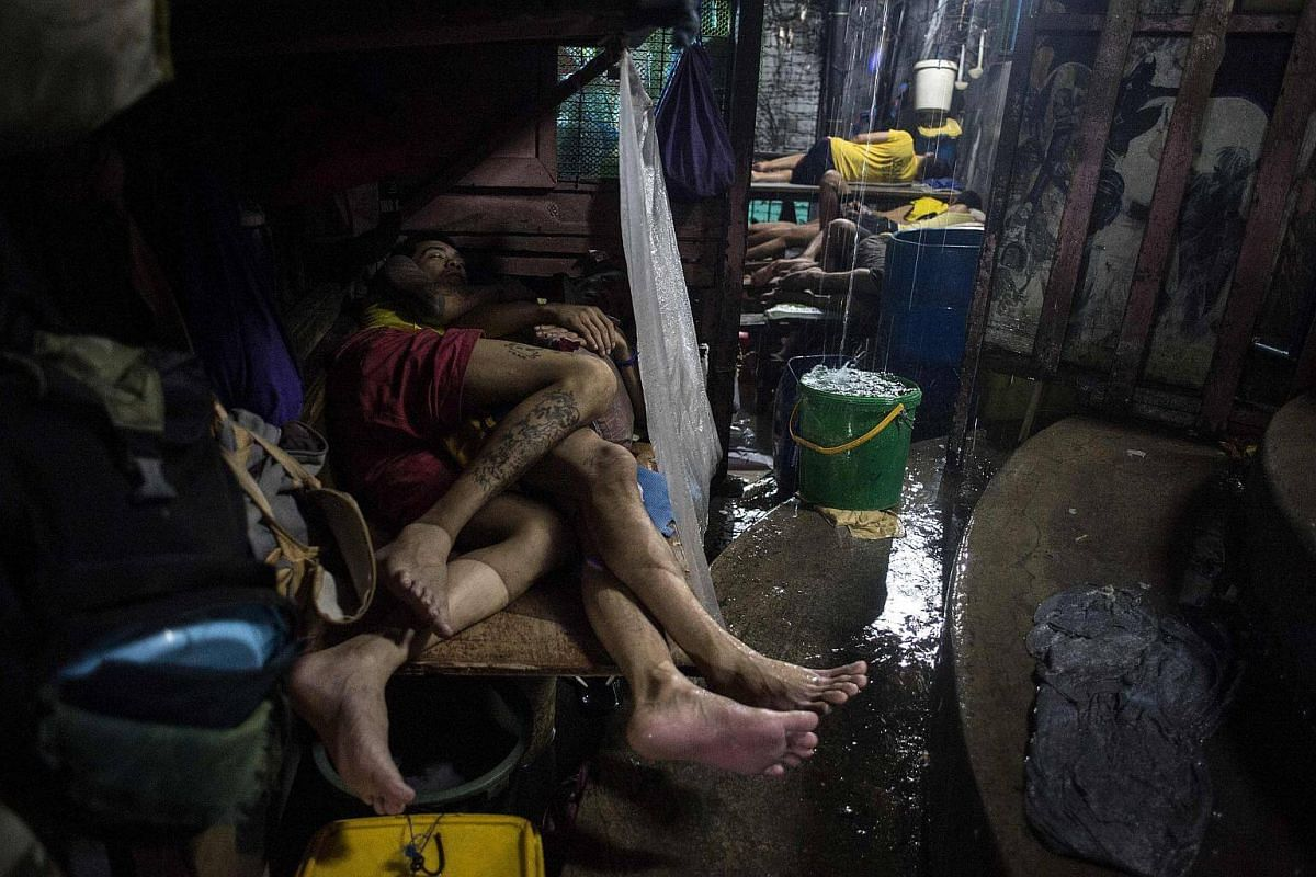 Inmates sleeping during a rainy night inside the Quezon City Jail in Manila on July 27, 2017.