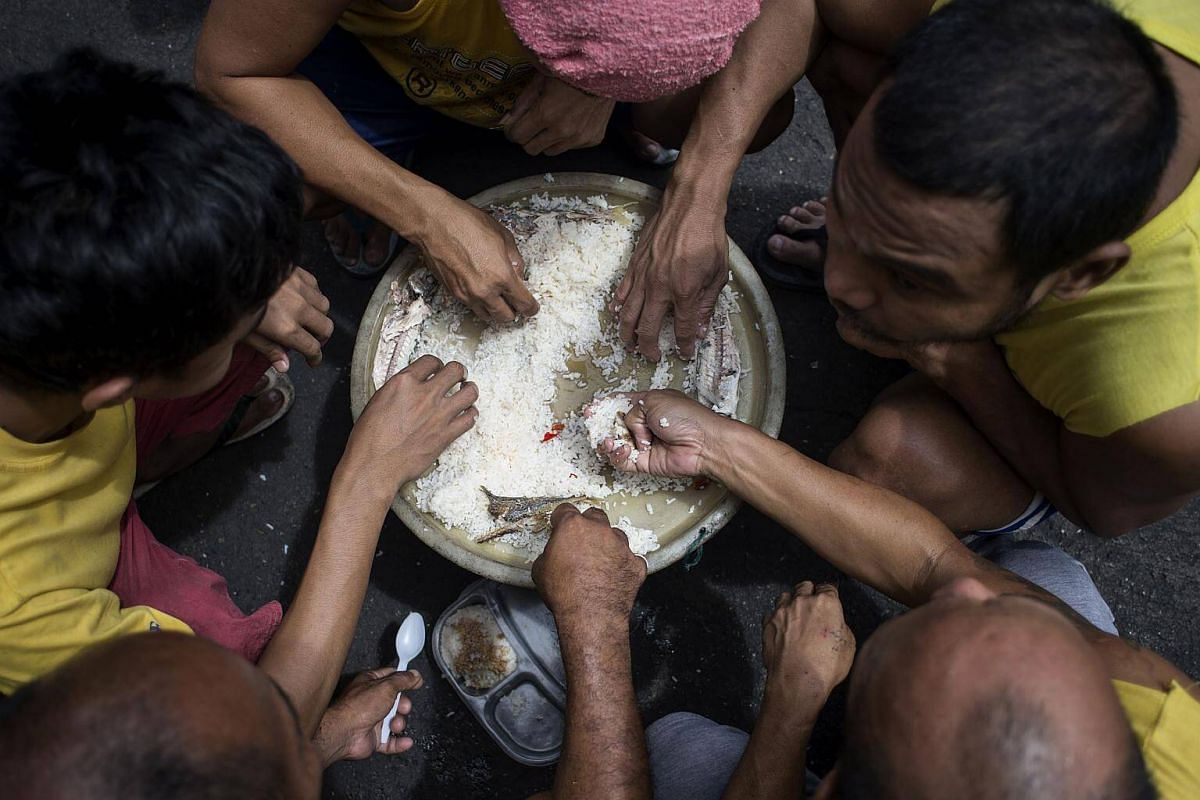 Inmates eating their lunch inside the Quezon City Jail in Manila on July 11, 2017.