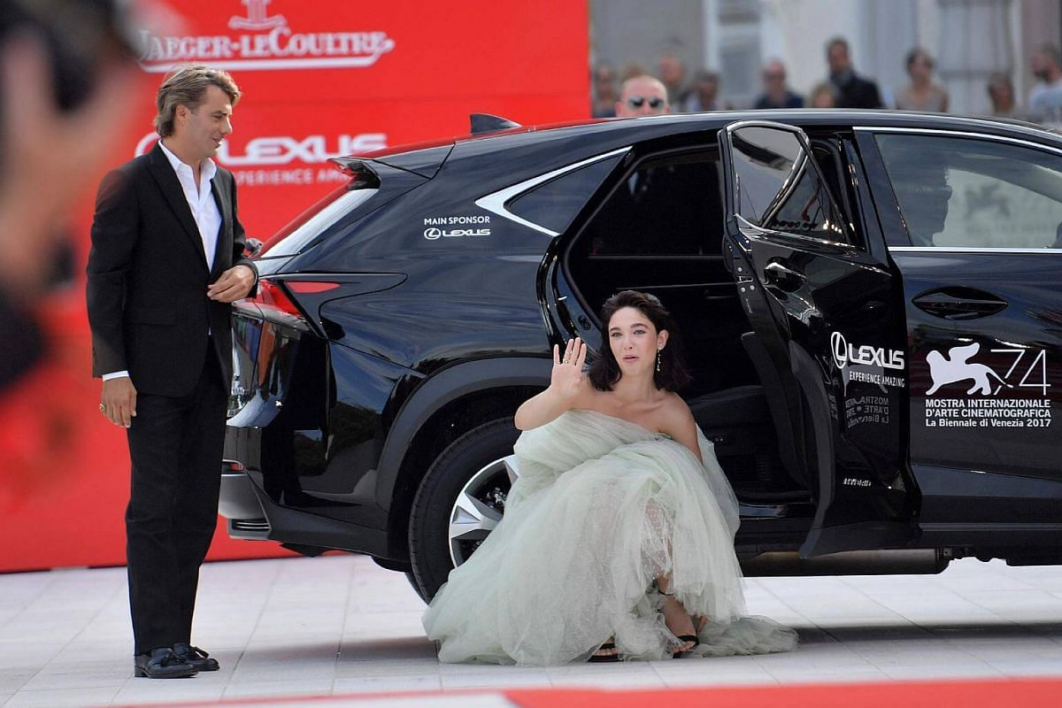 Actress Matilda de Angelis adjusts her shoe as she arrives at the premiere of the movie Una Famiglia presented in competition at the 74th Venice Film Festival at Venice Lido, on Sept 4, 2017.