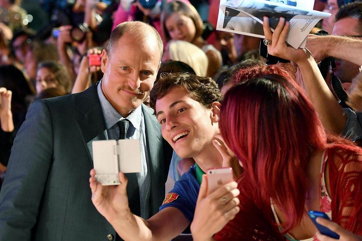 Actor and cast member Woody Harrelson (left) takes selfies with fans as he arrives for the premiere of Three Billboards Outside Ebbing, Missouri during the 74th Venice Film Festival, in Italy, on Sept 4, 2017.