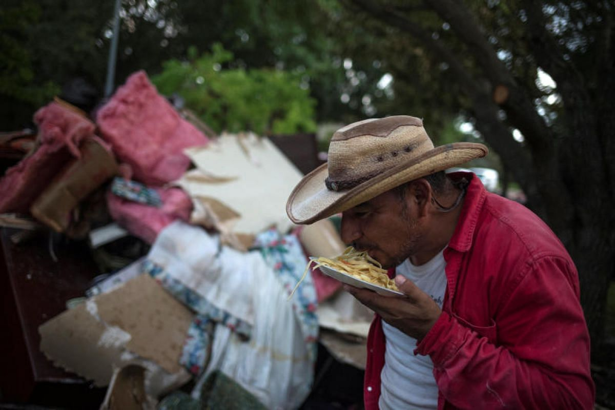 Mr Ruben Morales taking his dinner without utensils on Sept 4 after clearing furniture from the flood-hit house of a neighbour in Houston, Texas.