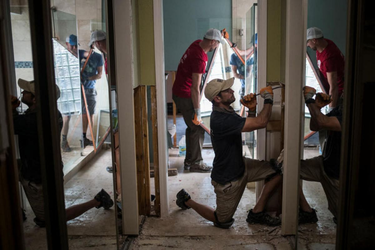 Samaritans  in Houston, Texas, helping to clear debris from the flood-damaged house of a neighbour on Sept 3.
