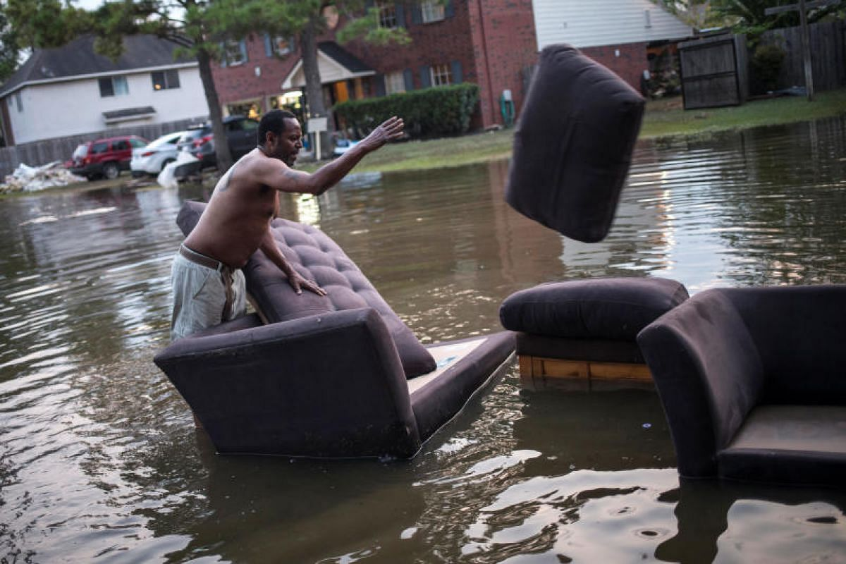 Mr Vince Ware moving his sofas onto the sidewalk from his house, which was left flooded by tropical storm Harvey in Houston, Texas, on Sept 3.