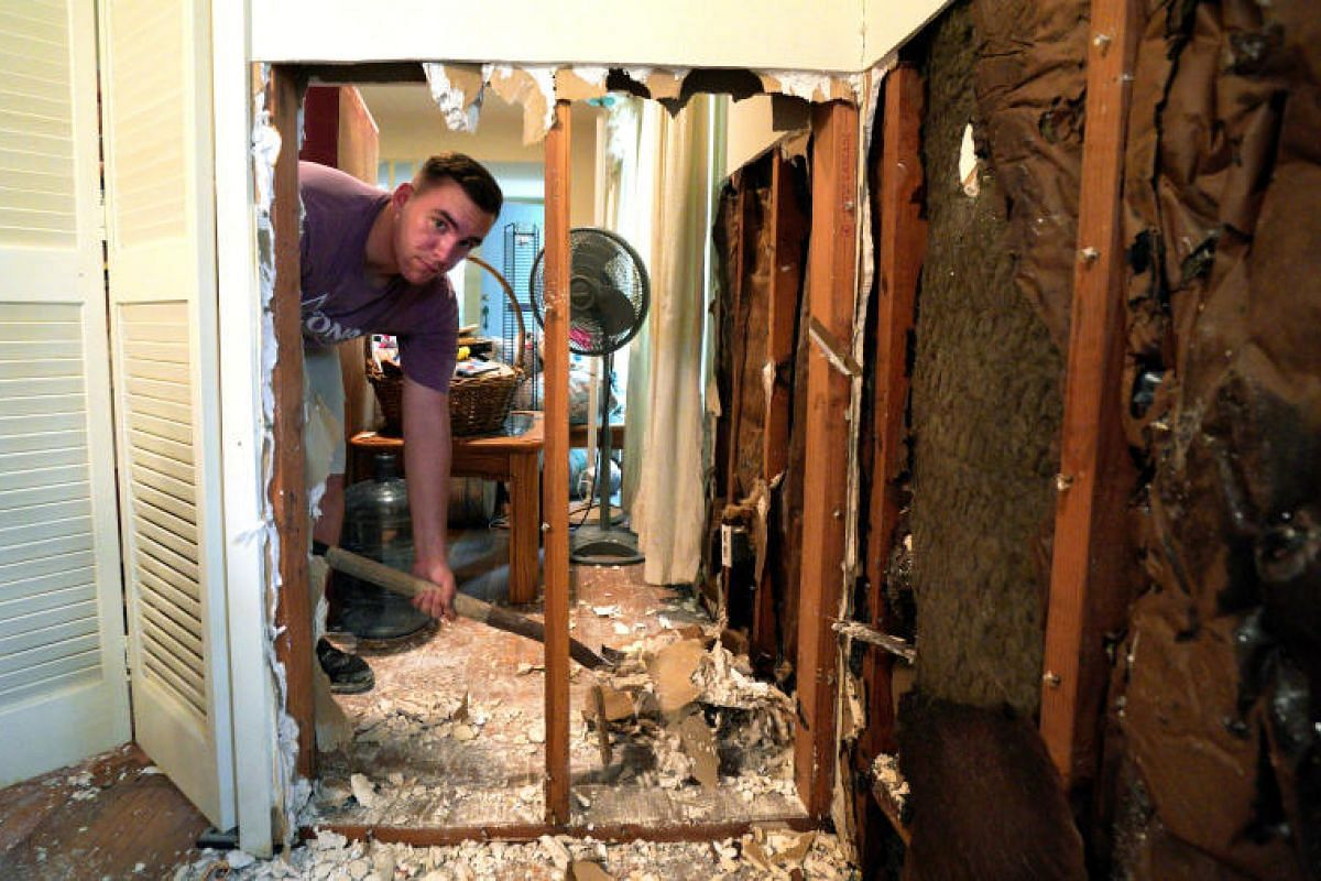 A volunteer from Texas A&M University helping to clean up the flood-damaged home of an alumnus in south-western Houston, Texas, on Sept 2.