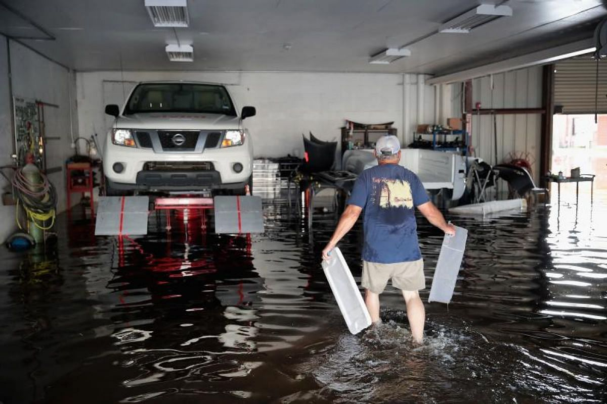 A man cleaning up an auto shop in Orange, Texas, on Sept 3 after torrential rain pounded south-east Texas following Hurricane Harvey, which caused widespread flooding.