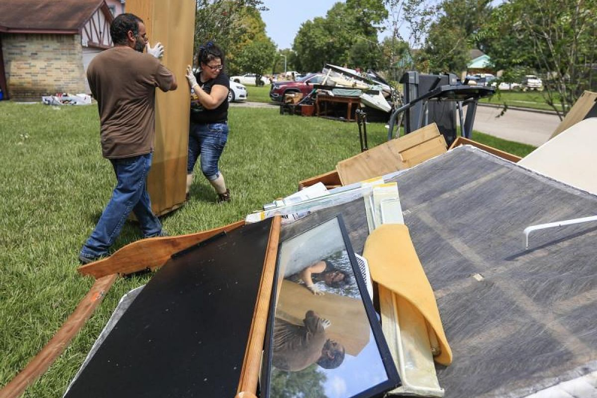 A couple carrying a damaged bookcase from their flood-hit east Houston home on Sept 1, as they began the clean-up process in the aftermath of Hurricane Harvey in Houston, Texas.