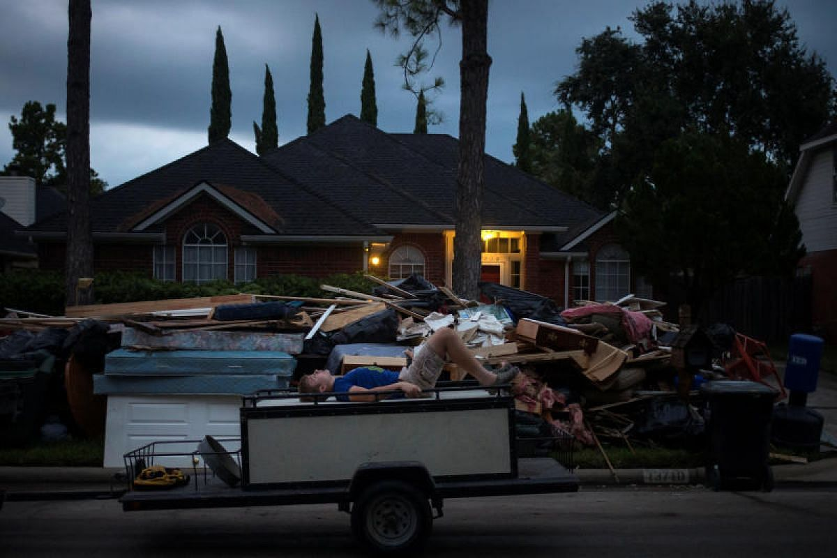 A boy lying on a piece of furniture on the back of a trailer while passing by debris outside a house flooded by tropical storm Harvey in Houston, Texas, on Sept 4.