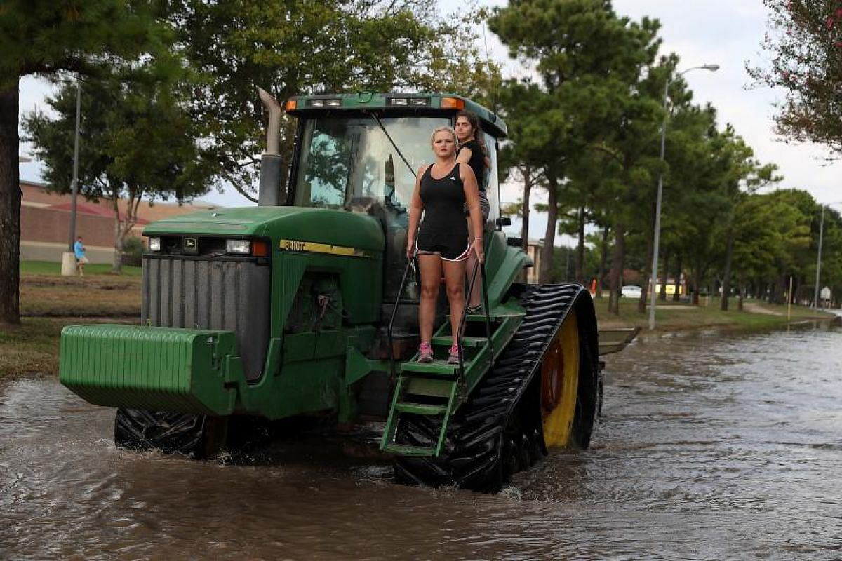 Two girls riding through floodwaters on a tractor in Katy, Texas, on Sept 4. Over a week after Hurricane Harvey hit southern Texas, residents are beginning the long process of recovering from the storm.
