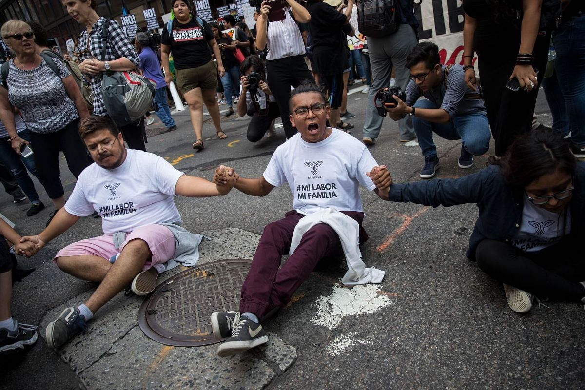 Immigration activists protesting the Trump administration's decision on the Deferred Action for Childhood Arrivals program sit in the street and block traffic on 5th Avenue near Trump Tower, September 5, 2017. PHOTO: GETTY IMAGES/AFP
