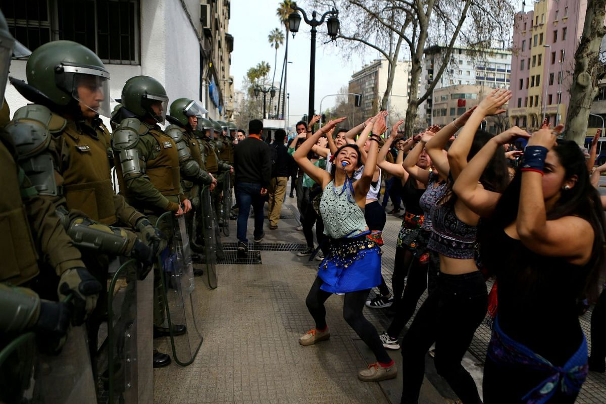 Demonstrators perform a dance in front of riot policemen during a march called by students to request changes in the education system in Santiago, Chile September 5, 2017. PHOTO: REUTERS