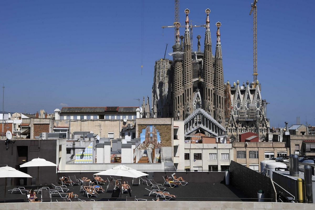 Tourists sunbathe on the terrace of an hotel with the Sagrada Familia in background in Barcelona on September 5, 2017. PHOTO: AFP