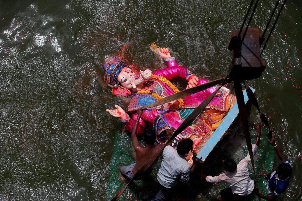 Devotees immerse an idol of the Hindu god Ganesh, the deity of prosperity, into the Sabarmati river on the last day of the Ganesh Chaturthi festival in Ahmedabad, India on Sept 5, 2017.