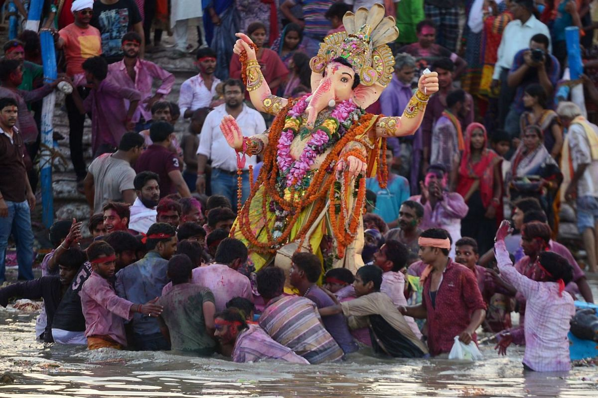 Devotees carry an idol of the elephant-headed Hindu god, Lord Ganesha, for immersion in a pool near Sangam in Allahabad on Sept 5, 2017.