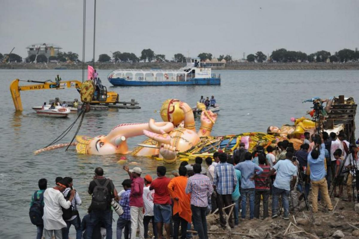 Devotees watch as crane workers immerse a 57-foot high statue of Hindu god Ganesh in the Hussain Sagar Lake during the Ganesh Chaturthi festival in Hyderabad, on Sept 5, 2017.