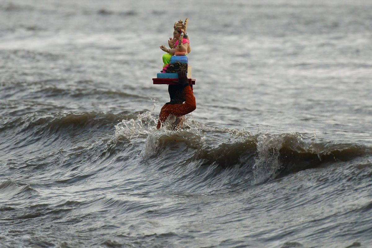 An Indian Hindu devotee carries an idol of the elephant-headed Hindu deity Ganesha for immersion at Dadar Chowpatty beach on the seventh day of the Ganesh Chaturthi festival in Mumbai on Aug 31, 2017.