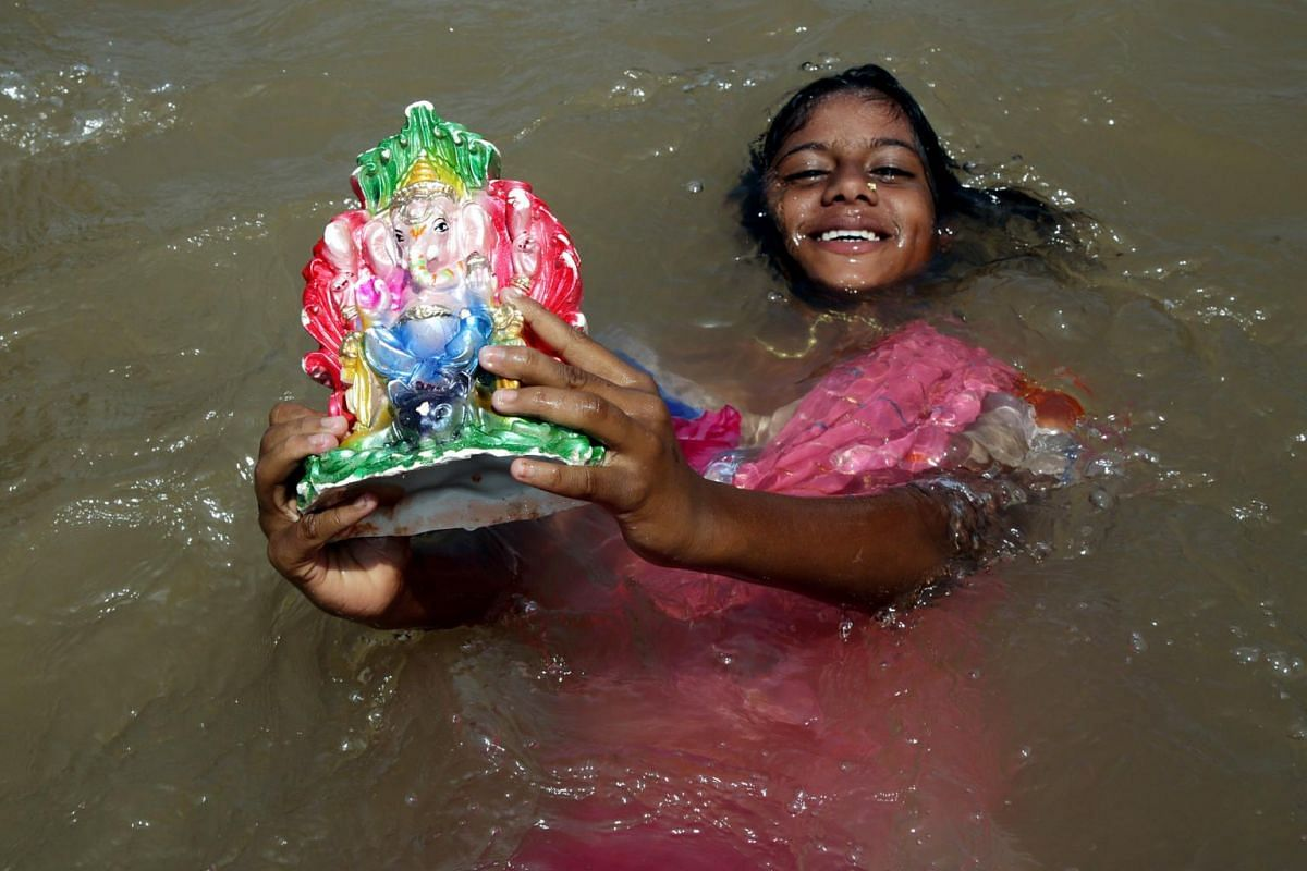 An Indian girl with an idol of Lord Ganesha, immersed by devotees into the Tawi River, as she searches for coins in the water in Jammu, the winter capital of Kashmir, India, on Sept 5, 2017.