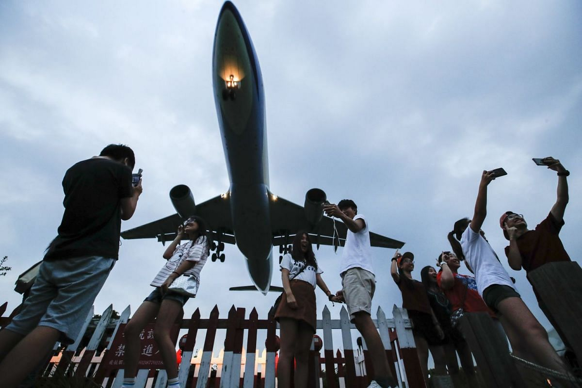 People take photos of an approaching C-130 military plane in Taipei, Taiwan, September 6, 2017. Plane spotting is a hobby of aircraft enthusiasts who track the movement of aircraft, recording details and taking photographs. PHOTO: EPA-EFE