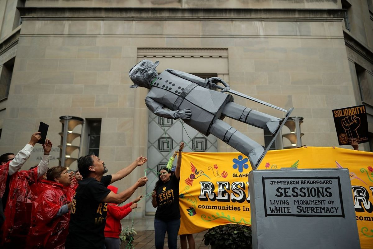 Protesters pull down a mock statue of Attorney General Jeff Sessions in front of the Department of Justice to demonstrate against the Trump Administration's decision to end the 2012 Deferred Action for Childhood Arrivals (DACA) policy September 6, 20
