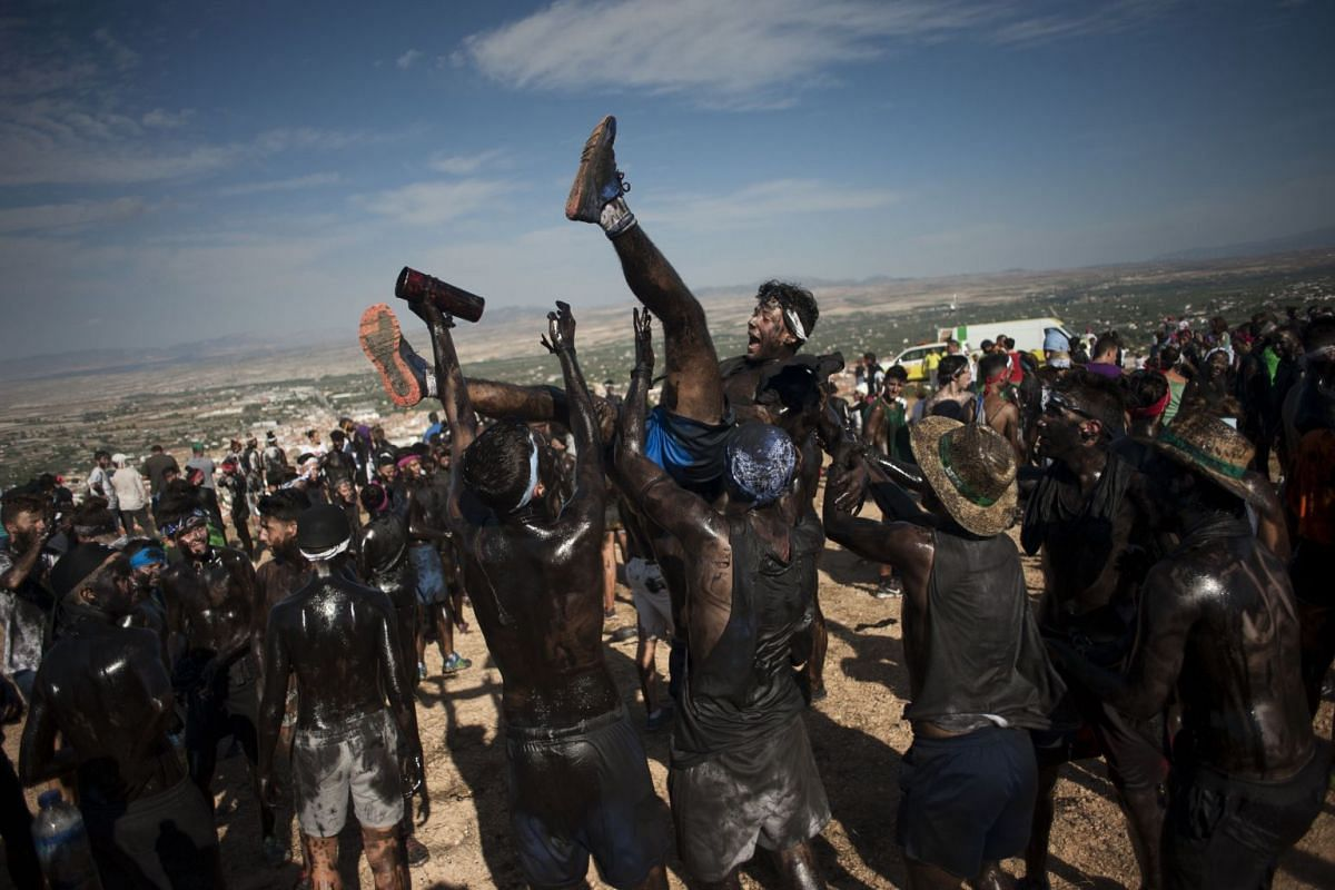People covered in black grease toss one another during the traditional festivities of the Cascamorras, in Baza, near Granada, on September 6, 2017. PHOTO: AFP