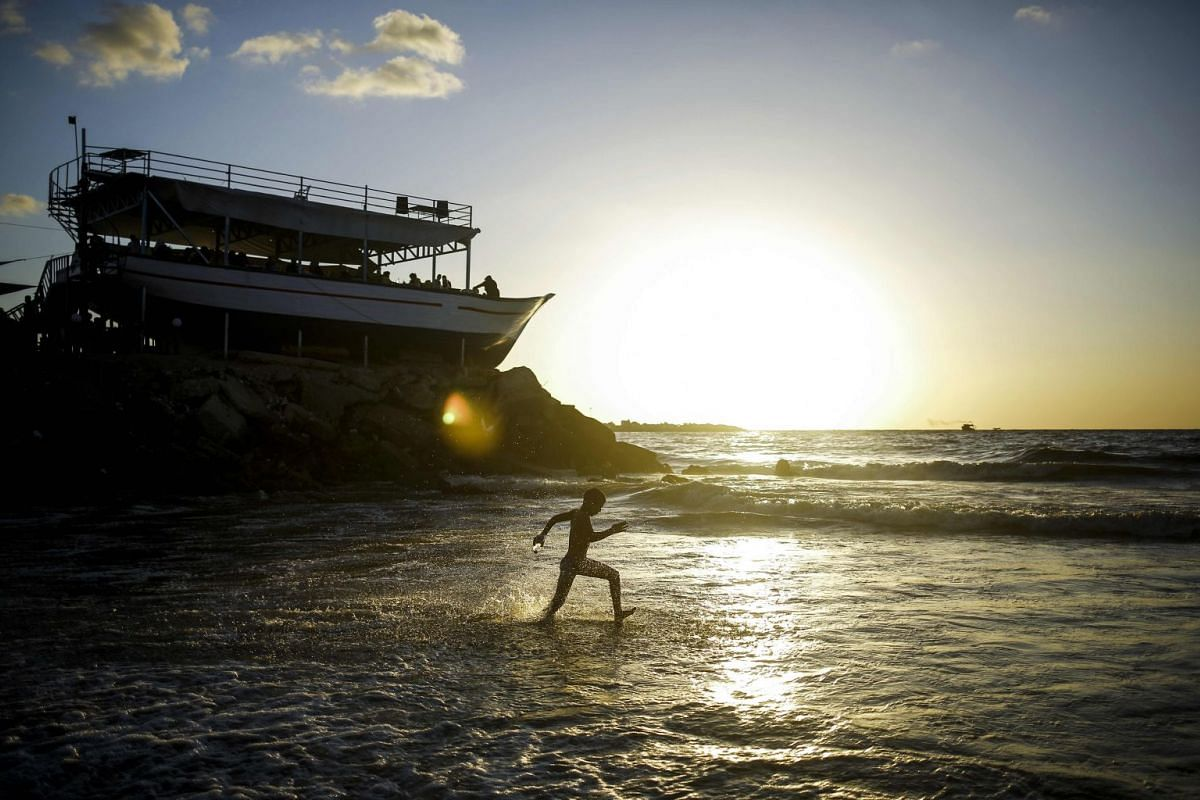 A Palestinian boy runs through the water at the beach at sunset in Gaza City on September 6, 2017. PHOTO: AFP