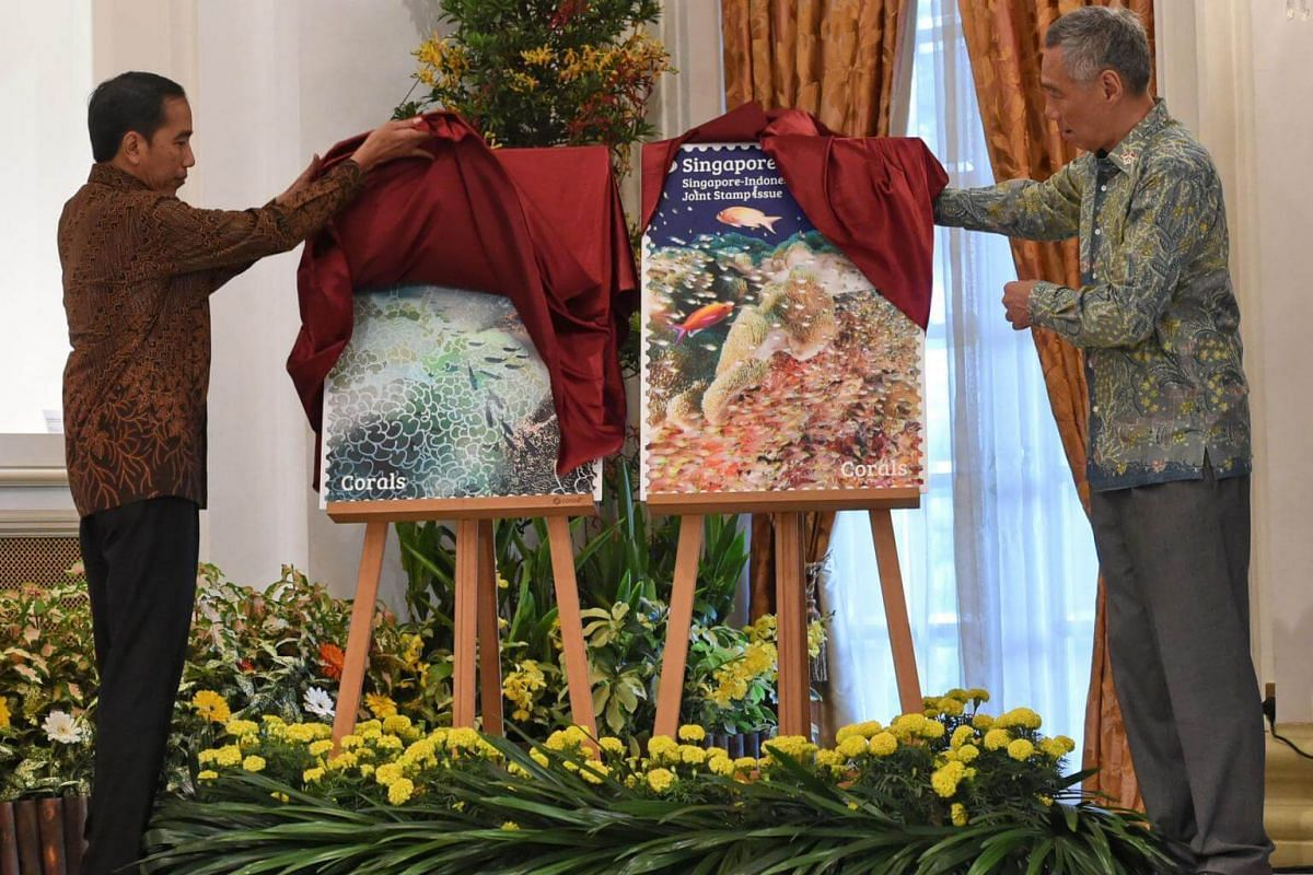 Indonesian President Joko Widodo (left) and Singapore Prime Minister Lee Hsien Loong (right) officiate the launch of the commemorative stamps between both countries at Istana Presidential palace in Singapore on Sept 7, 2017.