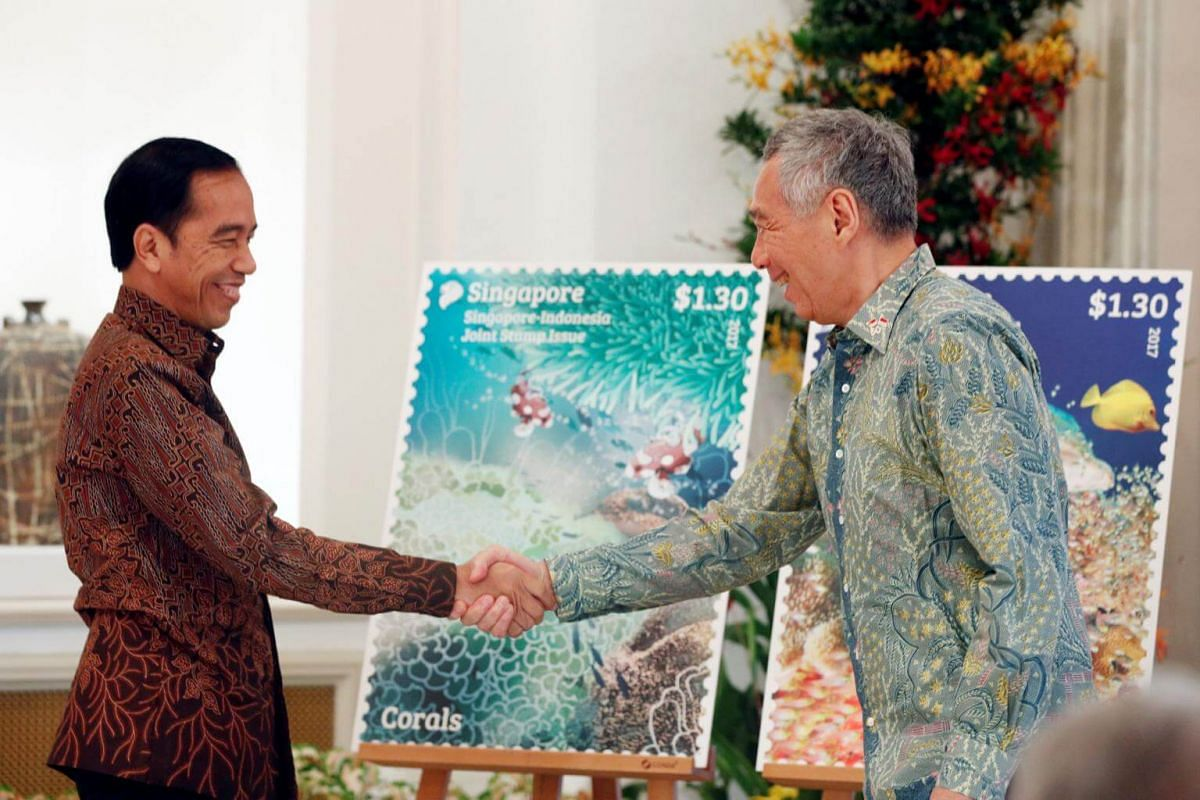 Indonesia's President Joko Widodo and Singapore's Prime Minister Lee Hsien Loong unveil a joint stamp issue at the Istana in Singapore on Sept 7, 2017.