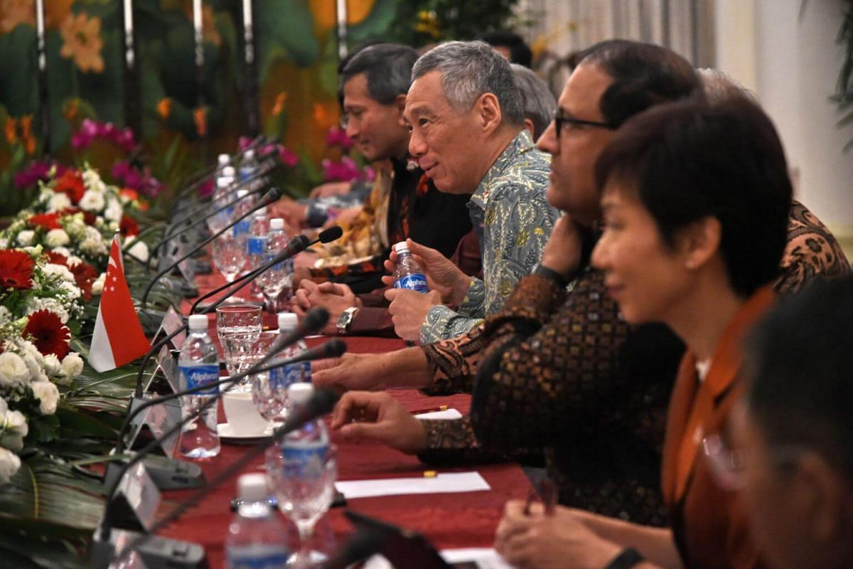 Singapore Prime Minister Lee Hsien Loong (holding bottle) attends a delegation meeting with Indonesian President Joko Widodo (not pictured) at Istana Presidential palace in Singapore on Sept 7, 2017.