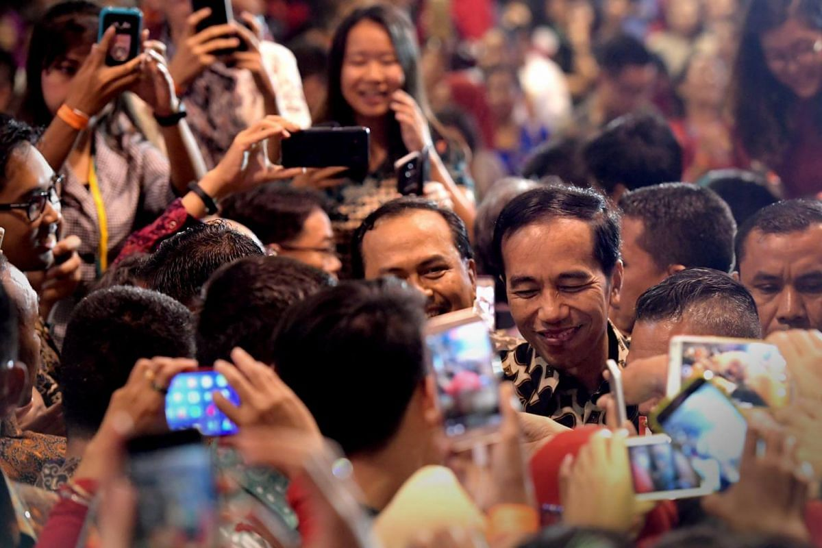 President Jokowi gets mobbed as he heads to the stage.