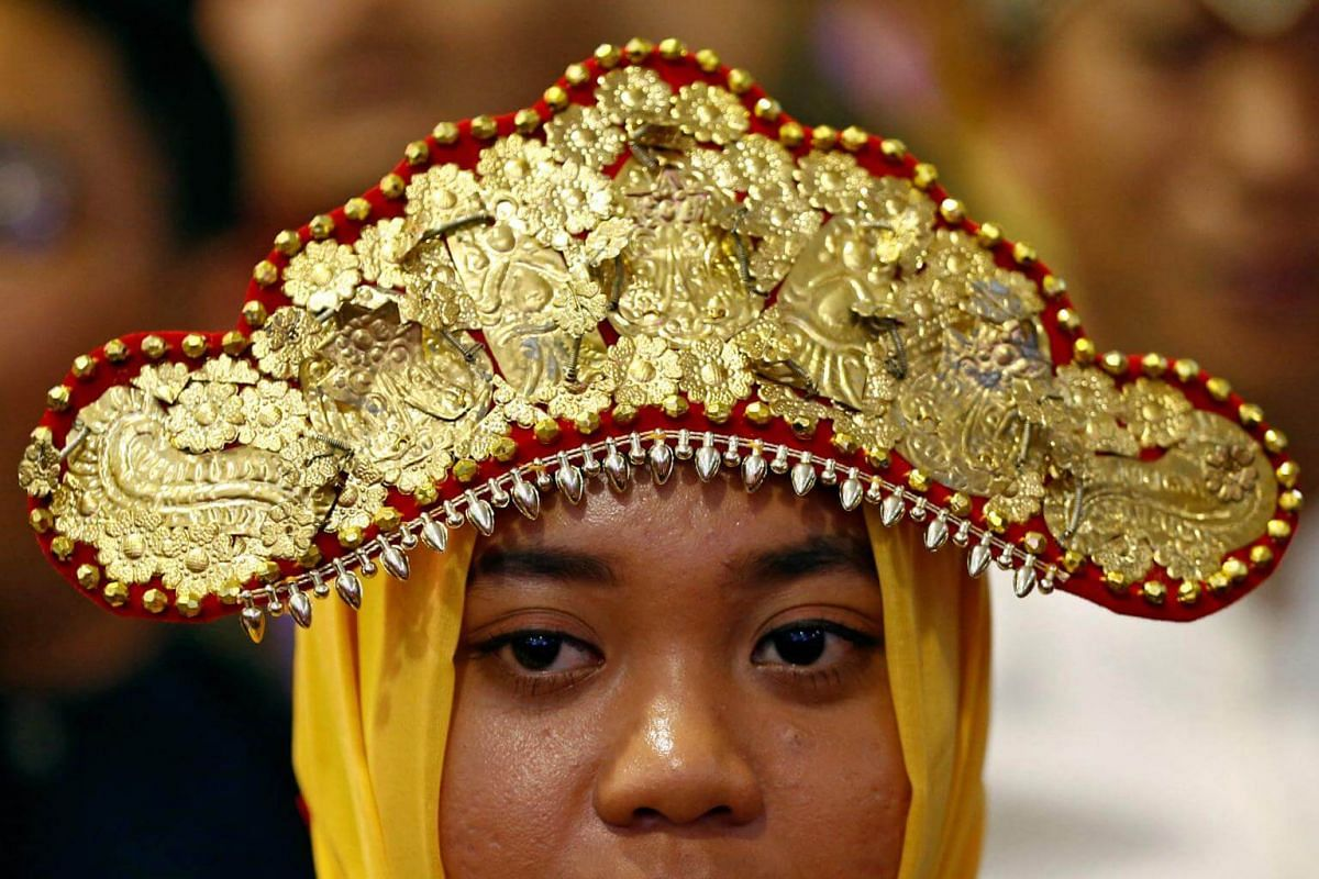 A woman dressed in her traditional costume waits for the arrival of Indonesian President Joko Widodo at the Indonesian embassy in Singapore on Sept 6, 2017.