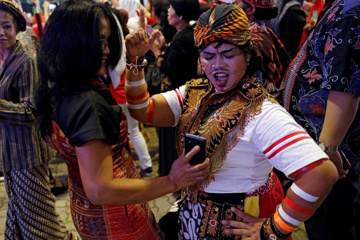 Domestic helper Triningsih, 43, of Semarang dances in her traditional costume with a crowd made up of largely domestic helpers, as they wait for the arrival of Indonesia's President Joko Widodo at the Indonesian embassy in Singapore on Sept 6, 2017.